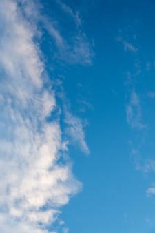 Естественный солнечный фон голубого неба с красивыми пухлыми белыми кучевыми облаками и пушистыми перистыми облаками. красивый естественный фон неба, вертикальная рамка