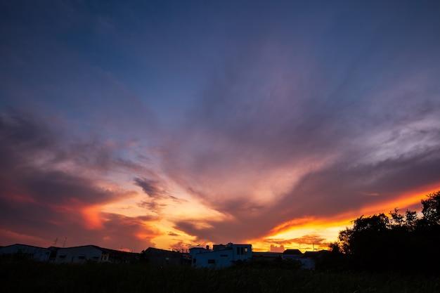 街の家の上の自然の日没の日の出。日没時の風光明媚なカラフルな空の下のオレンジ色の風景