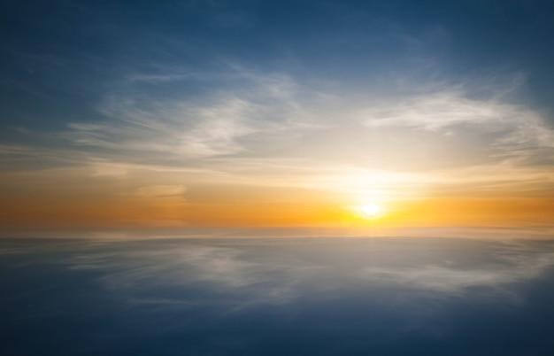 フィールドまたは牧草地の上の自然の日没の日の出。明るい劇的な空と暗い地面。日没の夜明けの日の出の風光明媚なカラフルな空の下の田園風景。サンオーバースカイライン、ホライゾン。温かみのある色。
