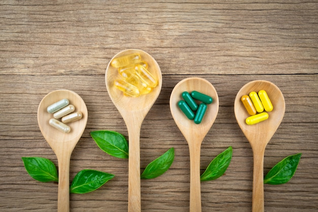 Natural supplements in capsule,from herbs on wood