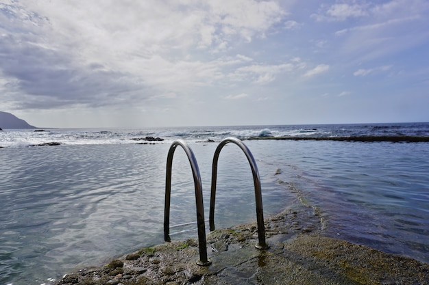Natural swimming pool of la maceta in the island of el hierro, canary islands, spain, during a summer sunset