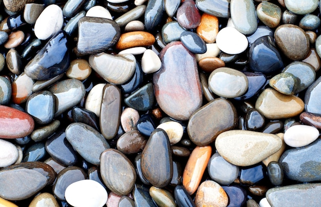 Natural texture background colorful sea stones in water top view