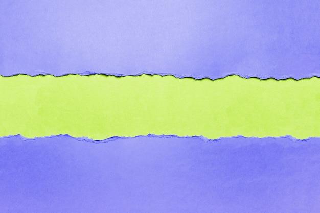 緑の上の自然な引き裂かれた青い織り目加工の紙。