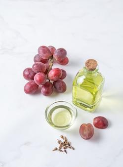 台所のテーブルの透明なボトルに入ったブドウの種子からの天然植物油。健康的な食生活。コピースペース