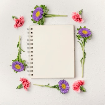 Natural violet and carnation flowers frame with notepad