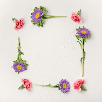 Natural violet and carnation flowers frame