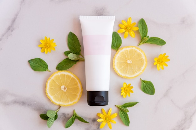 Natural vitamin c skincare product with fresh juicy lemon fruit slices on marble surface