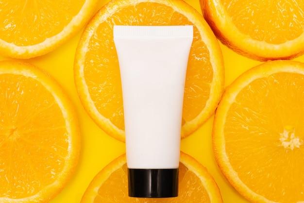 Natural vitamin c skincare products with fresh juicy orange fruit slice on orange