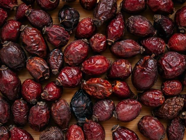 Натуральный витамин, пищевая добавка для здоровья. сушеные ягоды шиповника или rosa canina. сухие плоды шиповника или шиповника на деревянных фоне. здоровая и травяная концепция. выборочный фокус.