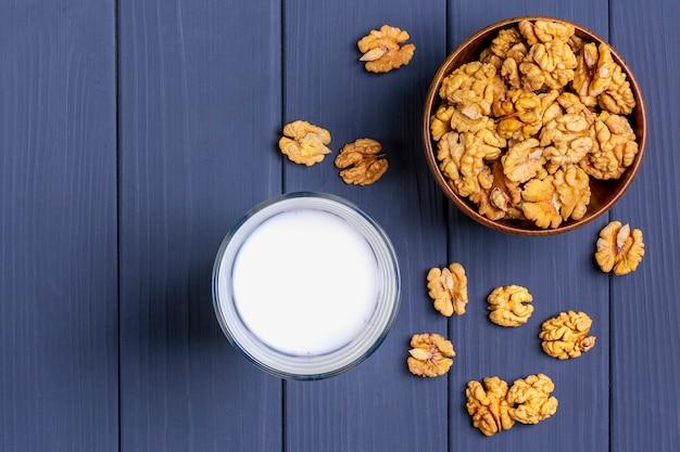Натуральное ореховое растительное молоко в стеклянной чашке и очищенные орехи в деревянной миске на темно-сером фоне