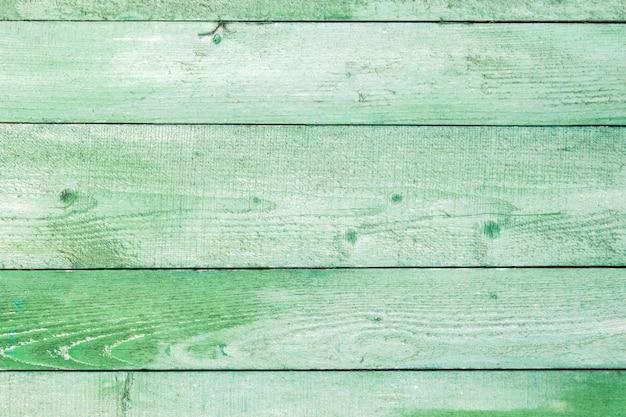 自然な風化した木の板の背景。緑のボードパネルに古い塗装