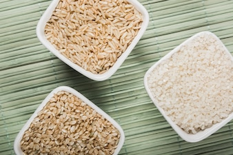Natural white; brown long and flat uncooked rice bowls on green placemat
