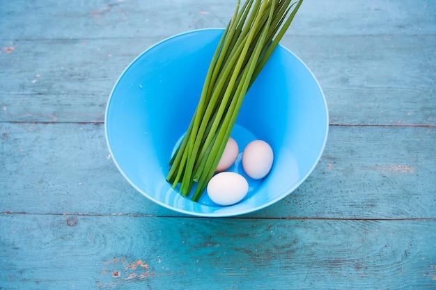 파란색 그릇에 자연 흰 계란과 오래 된 푸른 나무 테이블 위에 봄 양파
