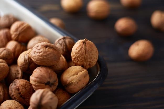 Натуральные цельные грецкие орехи на темном деревянном столе