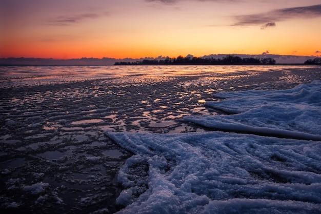 일몰시 해변에 자연 겨울 풍경입니다. 얼음과 일몰 하늘.
