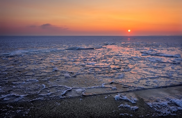 Natural winter landscape on seashore during sunset. ice and sunset sky.
