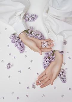 ライラックの花と花びらで作られた手のための自然な女性の化粧品。手の肌に潤いを与え、柔らかくします。ライラックの花が腕の袖から突き出ています