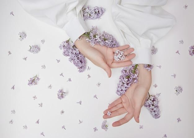 ライラックの花と花びらで作られた手のための自然な女性の化粧品。