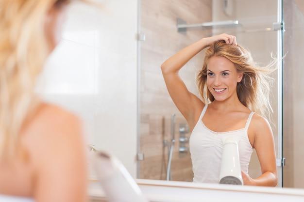 鏡の前で自然な女性が髪を乾かす