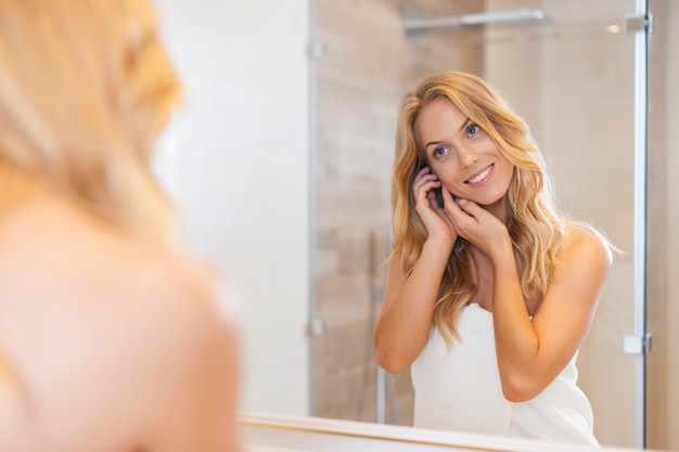 Natural woman looking herself reflection in mirror