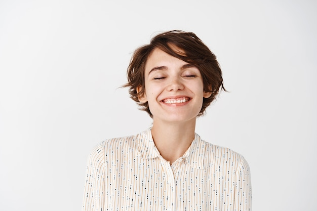 Natural woman with beautiful face, close eyes and smiling dreamy, imaging something positive, standing on white wall