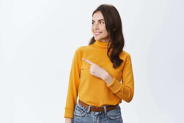 Естественная женщина с легким макияжем указывает и смотрит влево на место для копирования, показывая логотип на пустой белой стене, стоит в повседневной одежде у белой стены