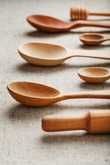 Natural wood spoons in a row on burlap fabric. natural natural materials. caring for the environment
