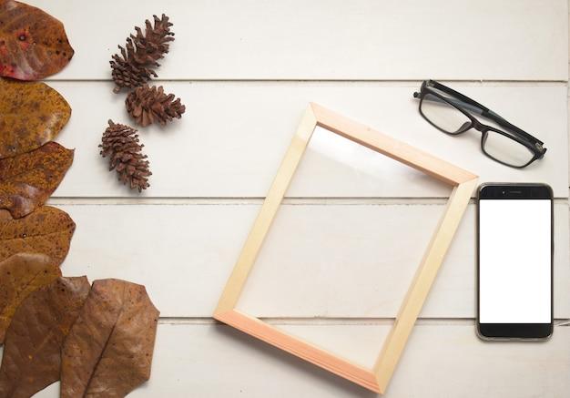 自然な木製フレームと白いテーブルの背景、上面図の概念に空白の画面とスマートフォン