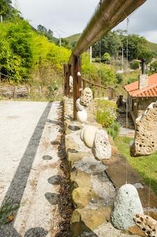 装飾的な吊るされた石が付いている自然な木製の手すり