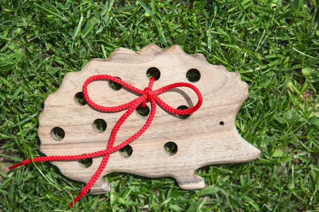 Natural wooden toy hedgehog in grass