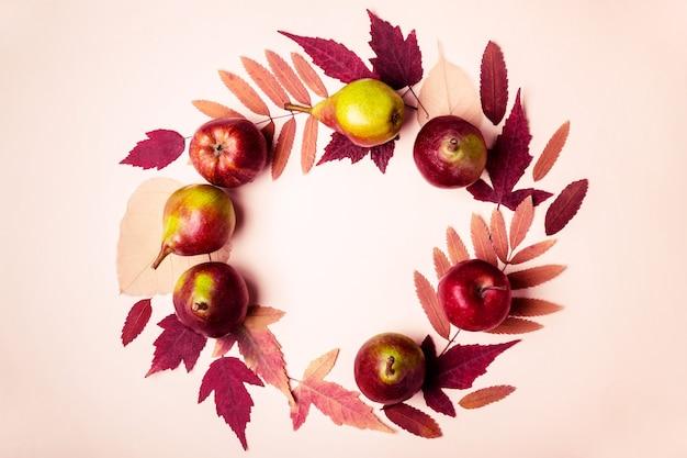 분홍색 배경에 마른 분홍색 잎과 배의 자연 화환. 가 수확 개념입니다.