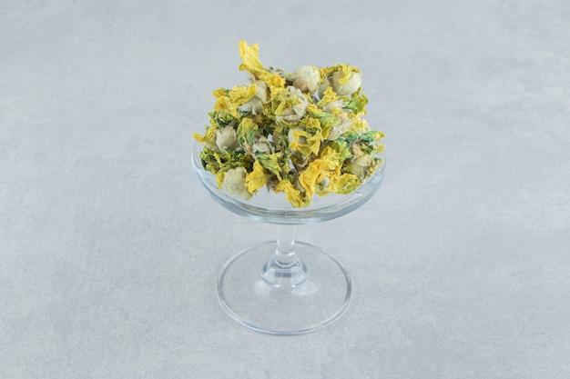 유리 접시에 자연 노란색 꽃입니다.
