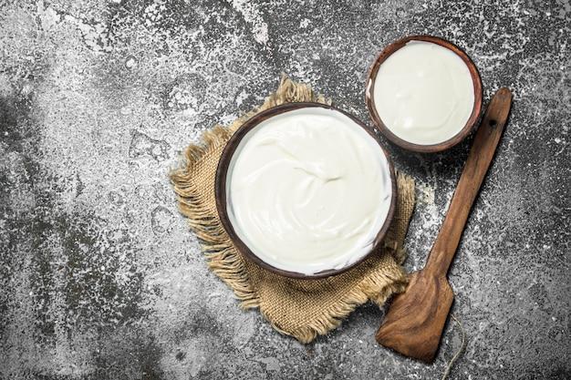 Натуральный йогурт в миске. на деревенском фоне.