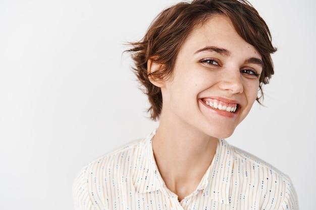 幸せな笑顔、陽気に見える、白い壁に立っている自然な若い女性