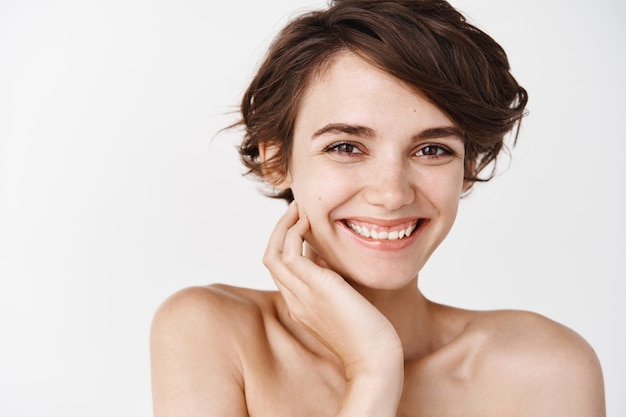 Natural young woman with no makeup and naked shoulders, smiling happy, touching hydrated clean skin, white wall