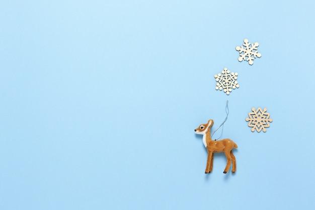 Натуралистическая игрушка косуля и три маленькие деревянные снежинки на пастельных синих, копией пространства.