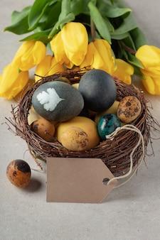 Естественно окрашенные пасхальные яйца в гнезде, желтые тюльпаны и пустой ярлык на сером столе