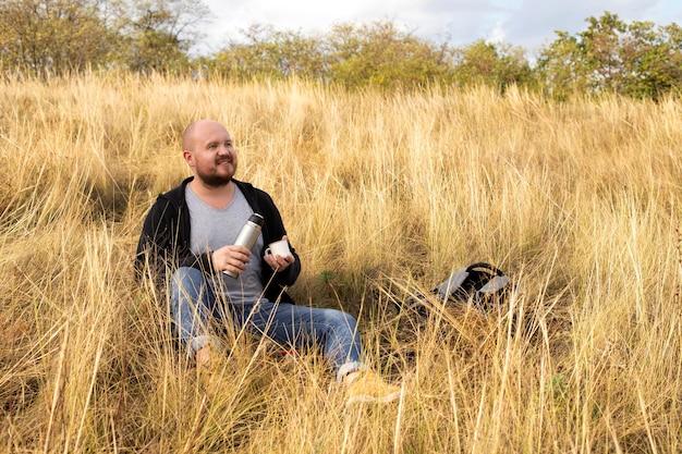 Природа, человек отдыхает на траве с чаем