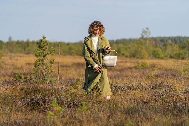 자연 가을 활동 젊은 여성이 바구니를 들고 행복한 미소를 짓고 있는 늪에서 크랜베리를 찾고 있습니다.