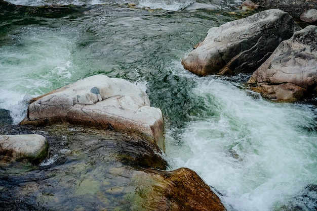 Nature background with cascades of mountain creek close-up