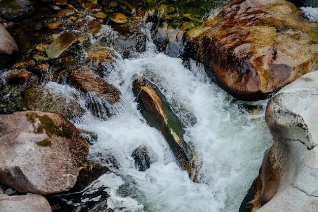 마운틴 크릭 클로즈업의 폭포와 자연 배경입니다. 녹색 물과 아름다운 산 시내와 아름다운 풍경. 작은 강에 녹색 물이있는 목가적 인 풍경. 빠른 물 흐름 근접 촬영.