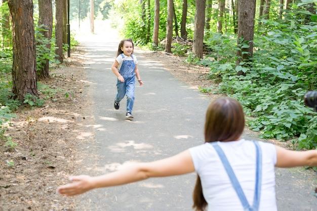 자연, 가족, 사람들 개념-아름다운 숲에서 사랑스러운 작은 아이 딸과 젊은 여자. 어머니에게 실행하는 딸.
