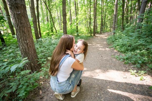 自然、家族、人々の概念-家族と自然の概念-美しいお母さんは彼女の小さなキスをします