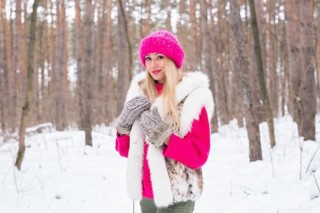 自然、ファッション、人々のコンセプト-冬の公園でポーズをとる若い魅力的な金髪の女性。