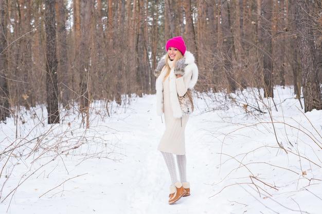 自然、ファッション、人々のコンセプト-ウィンターパークでポーズをとる若い魅力的な金髪の女性。
