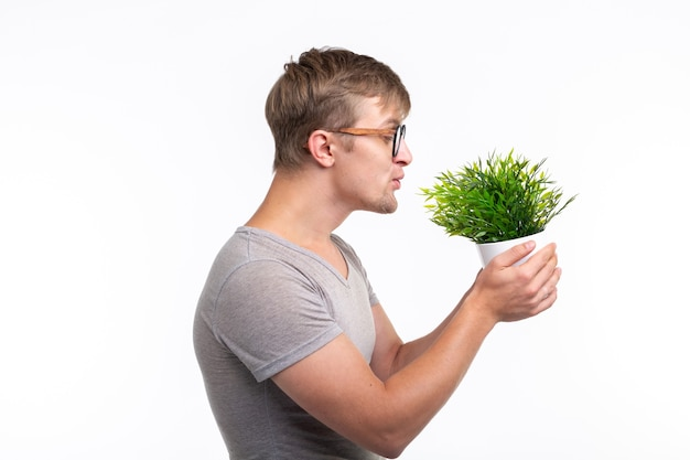 Nature, fun, fool around and nerd concept - portrait of funny young man kissing a plant