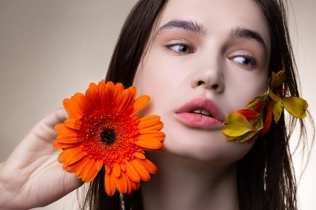 自然の重要性。花でポーズをとる自然の重要性を促進する青い目の魅力的な若いモデル