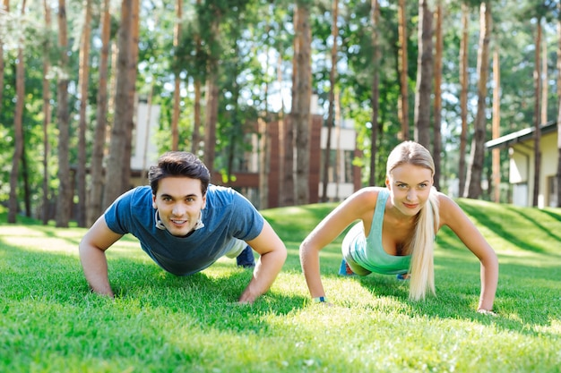 In the nature. joyful positive couple smiling while having an outdoor workout