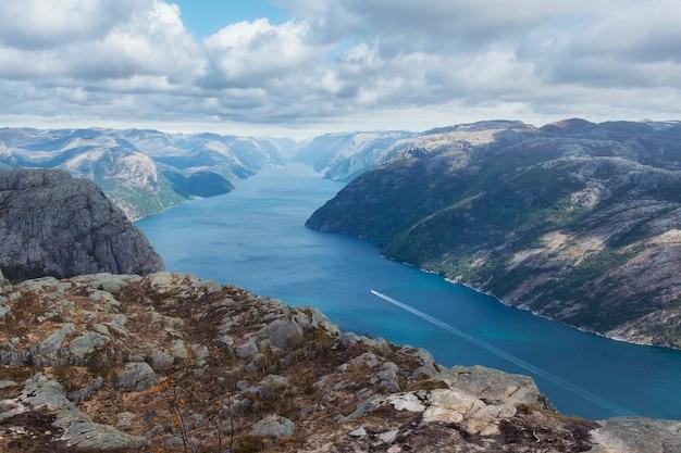 自然、ノルウェーの風景、ルセフィヨルドの上の岩が多い高原、春の日の船