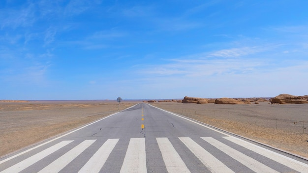 Nature landscape view of straight road in under sunny blue sky in dunhuang unesco global geopark
